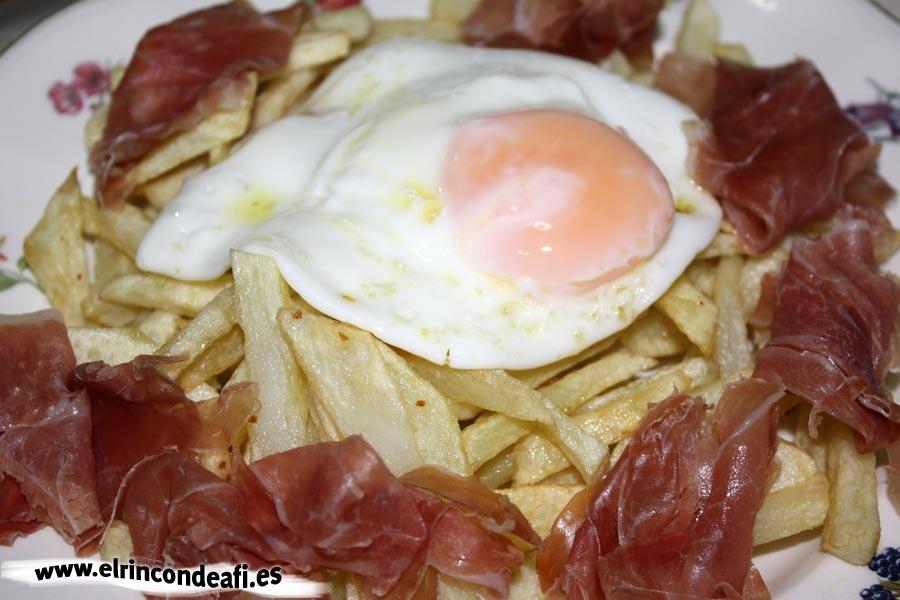 Huevos rotos con jamón, poner el huevo frito sobre las papas y el jamón