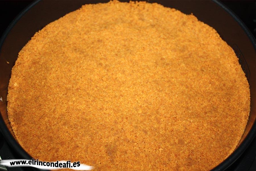 Tarta de tres colores, introducir en un molde las galletas trituradas y mezcladas con la mantequilla
