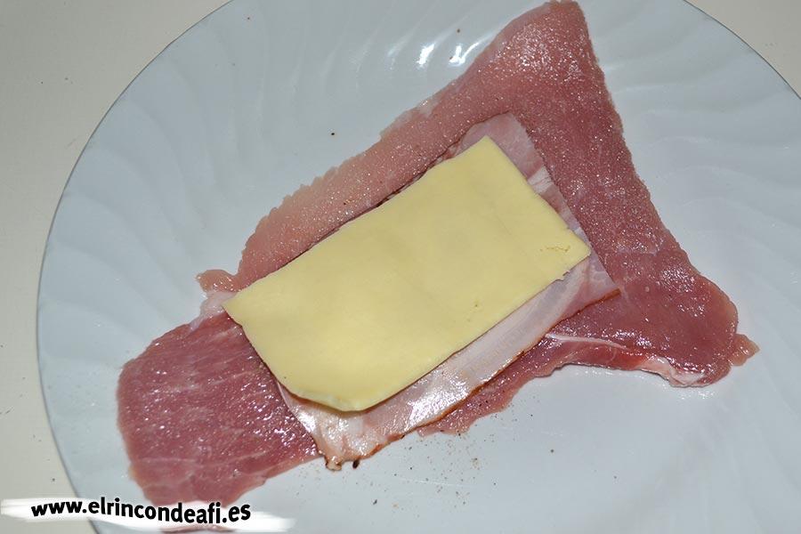 Enrolladitos de cerdo con bacon y queso, poner media loncha de queso