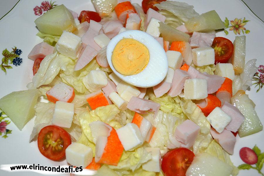 Ensalada de queso de cabra, pechuga de pavo y palitos de cangrejo con salsa rosa, añadirlos junto con trozos de melón y medio huevo cocido por persona