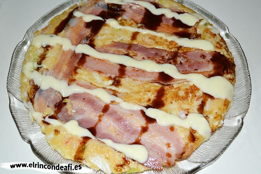 Okonomiyaki o pizza japonesa, decorar con mayonesa y la salsa de okonomiyaki