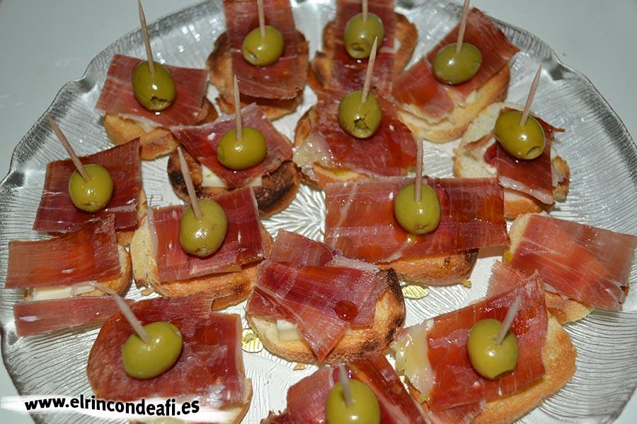 Tapa con jamón, queso brie y aceitunas, regar con aceite de oliva y decorar con aceituna