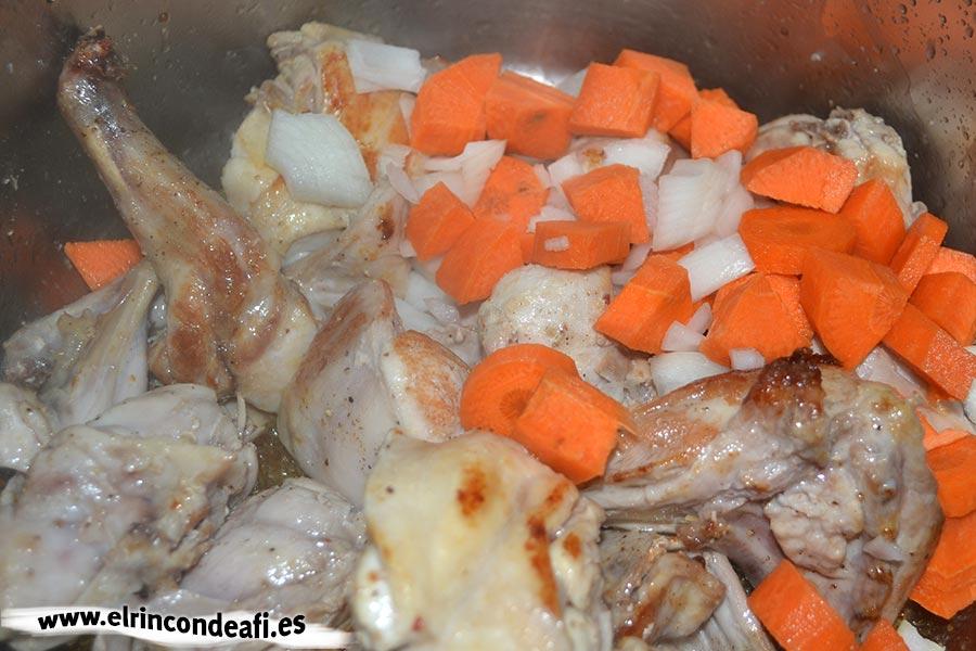 Arroz con conejo, añadir la cebolla y la zanahoria troceadas