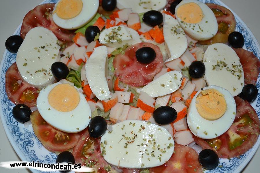 Ensalada de mozzarella de búfala y palitos de cangrejo, decoramos con aceitunas negras, orégano y escamas de sal