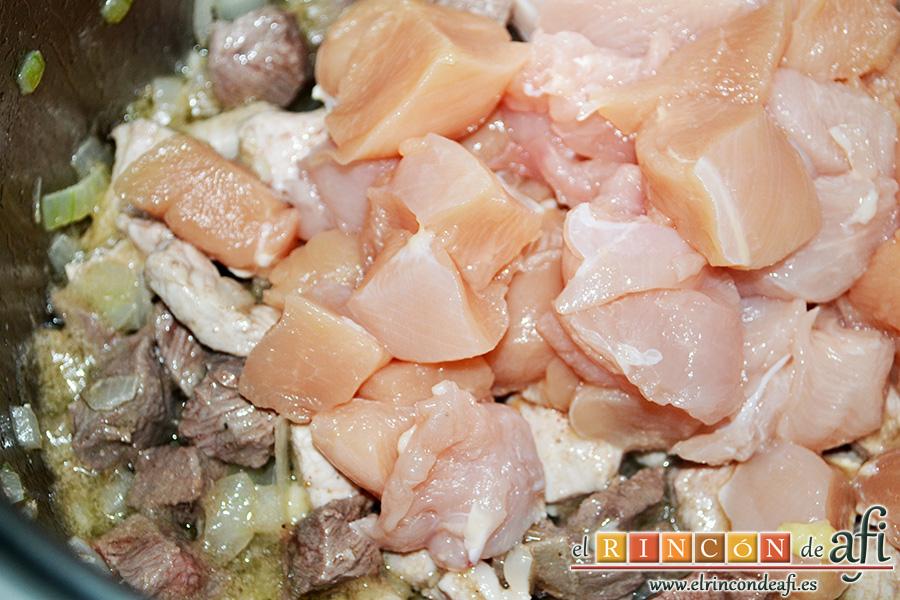 Paella tres carnes, añadir el pollo y remover