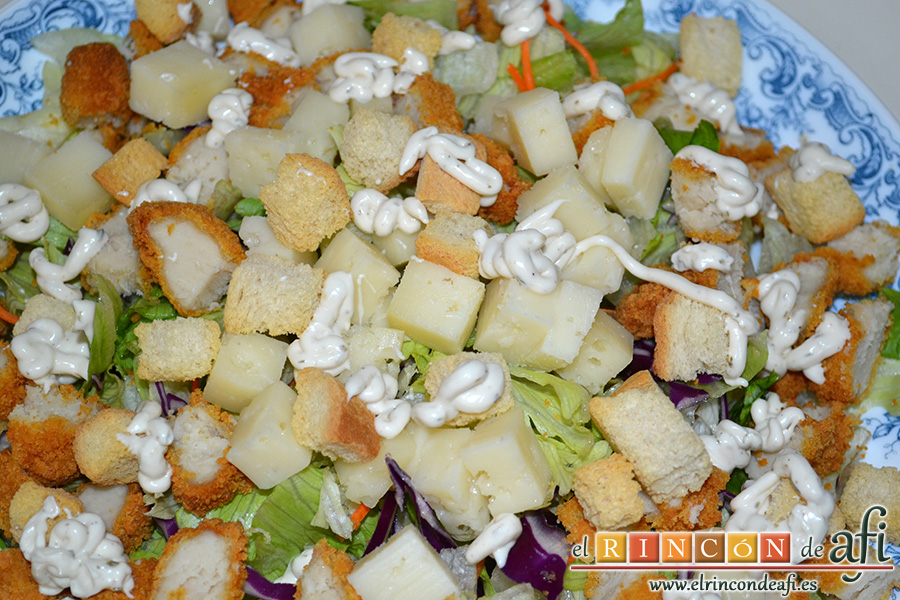 Ensalada César, añadir el pan tostado y los tacos de queso y aliñamos con la salsa César