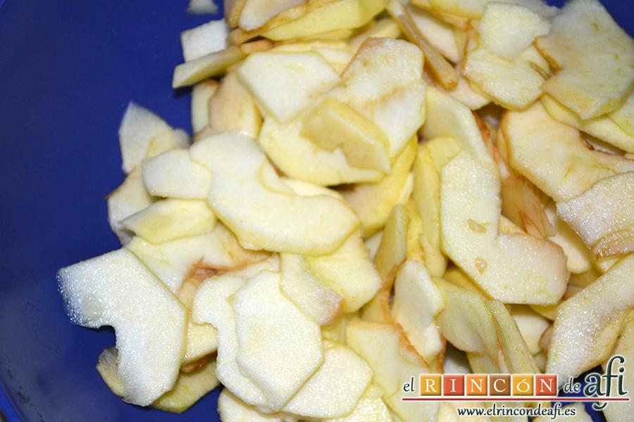 Bizcocho con manzanas, pelamos las manzanas, las cortamos en cuartos, las descorazonamos y las cortamos en láminas finas, y les añadimos el zumo del limón y el coñac