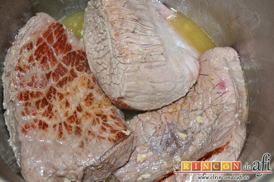 Carne guisada a la gallega, en una olla exprés, bien caliente añadimos unas cucharadas de aceite de oliva y seguidamente los trozos de carne y dejamos que se doren bien por todas partes