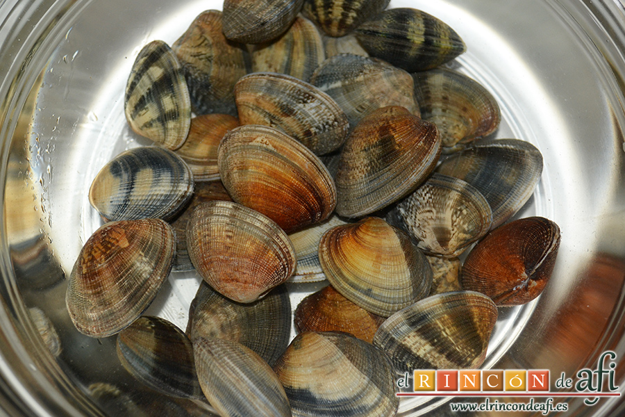 Fideos con almejas y gambones, ponemos las almejas en un bol con agua bien fría y sal una media hora antes de usarlas para que expulsen la arena