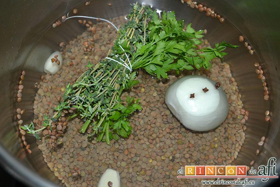 Lentejas al curry, lo introducimos en la olla junto con los ajos, una cebolla con los clavos pinchados para poder retirarlos una vez finalizada la cocción, un puñadito de sal y cubrimos con bastante agua