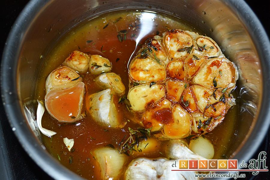 Lomo de cerdo al horno con queso manchego y membrillo, aprovechamos el jugo del asado y los ajos, sacándoles la piel para hacer una salsa colocándolos al fuego en un cazo. Añadimos el vino dulce