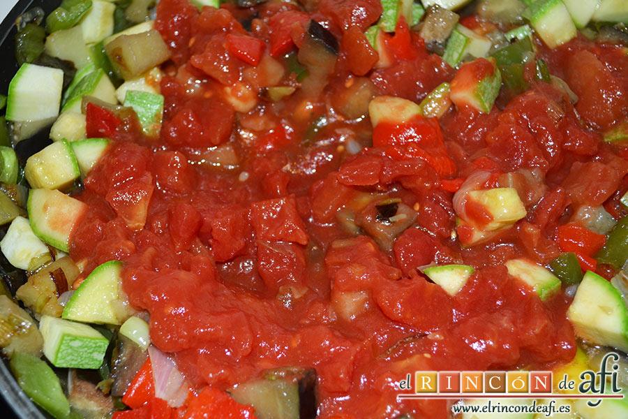 Pisto con papas y huevos fritos, añadir el tomate troceado y el pimiento rojo troceado