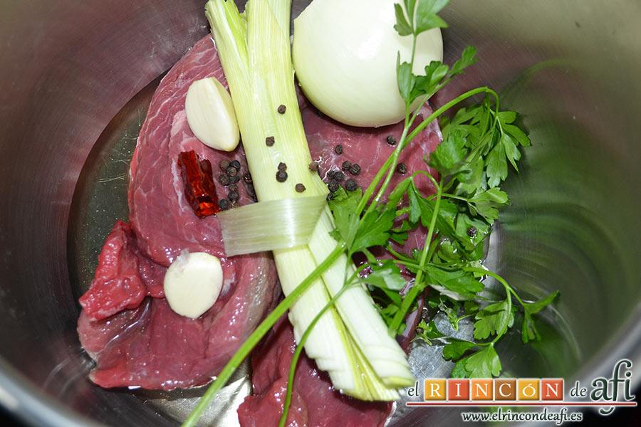 Frittata de morcillo y pimientos, en una olla exprés ponemos un chorro de aceite de oliva, el morcillo, un trozo de pimienta picante, los granos de pimienta negra, 1 cebolla, los 2 dientes de ajo, unas ramitas de perejil fresco y la parte verde de 1 puerro