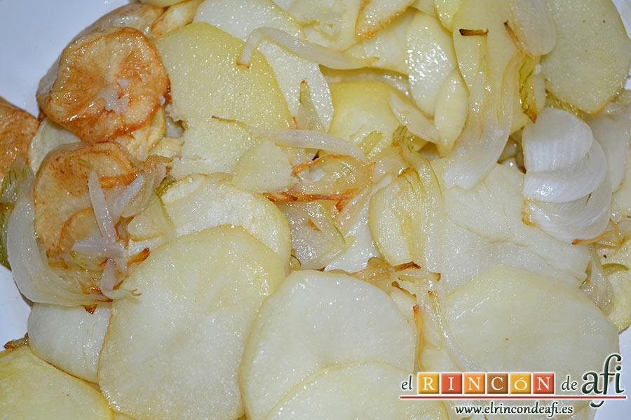 Bacalao gratinado con base de tomate, cortamos las papas peladas en rodajas y las cebollas en aros y las freímos con una pizca de sal en abundante aceite de oliva