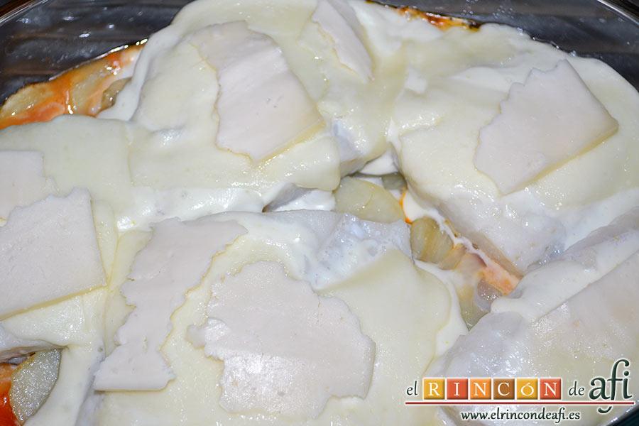 Bacalao gratinado con base de tomate, añadimos la mayonesa sobre los lomos de bacalao para terminar con las lonchas de queso