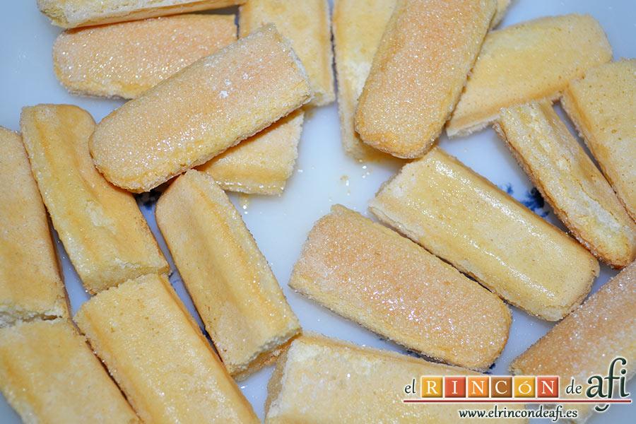 Tiramisú de mango, colocar el zumo de naranja en un plato e ir añadiendo los bizcochos cortados en dos para empaparlos