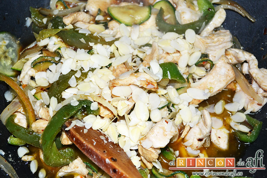 Cintas al wok con pollo y verduras, removemos todo bien y añadimos las almendras laminadas