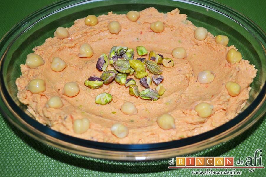 Hummus con pimientos y pistachos, colocamos la mezcla en un recipiente adecuado extendiéndola con una cuchara dejando unos círculos en la zona del medio y decorándolo con los garbanzos y los pistachos que teníamos reservados