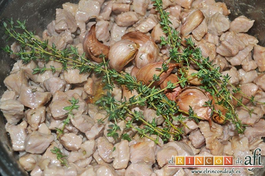 Cochifrito con papas brutas, cuando esté toda la carne bien frita le añadimos los dientes de ajo reservados con las ramas de tomillo fresco