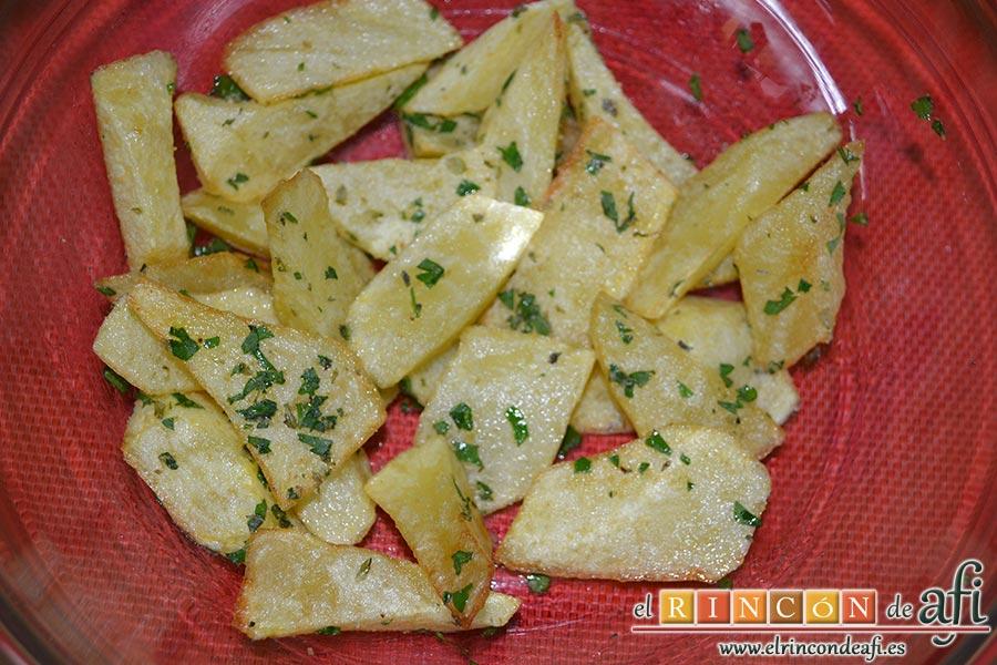 Cochifrito con papas brutas, cuando estén las papas bien fritas las ponemos en un bol y les añadimos la mezcla de las especias, sal y removemos bien