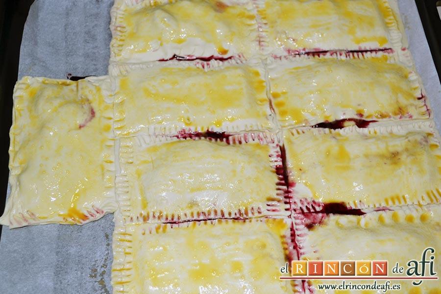 Empanadillas de cerezas y chocolate, pintar las láminas de hojaldre con el huevo batido ayudándonos de un pincel de cocina