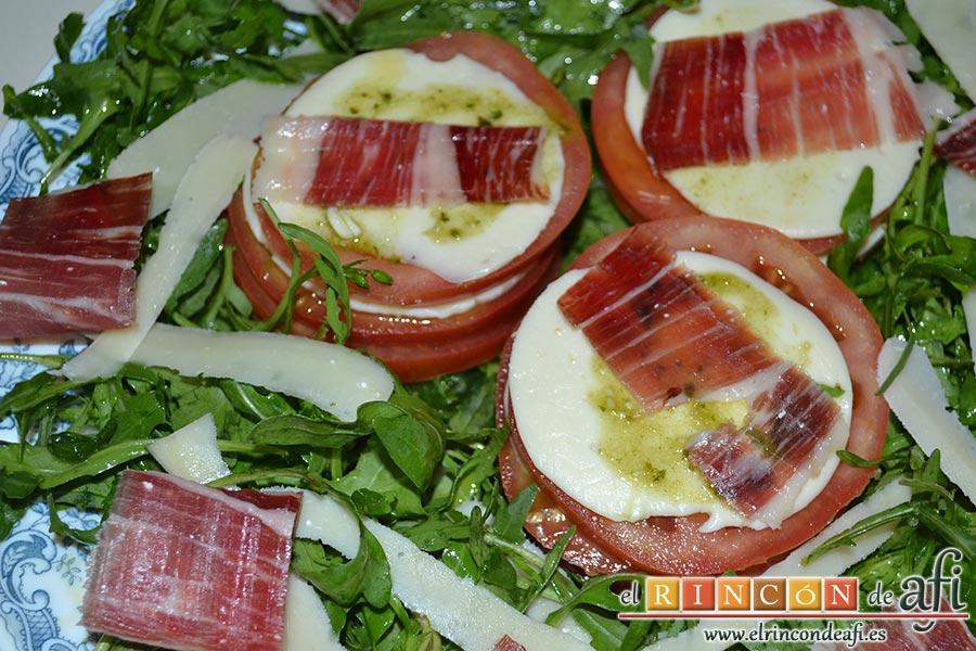 Ensalada de rúcula, tomate, queso gorgonzola, jamón y huevos de codorniz, colocamos un poco de vinagreta sobre el queso gorgonzola y colocamos las lonchas de jamón