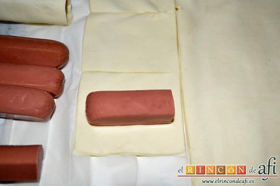 Aperitivo de hojaldre con salchichas o bacon, cortar las salchichas por la mitad y colocarla sobre un rectángulo de hojaldre