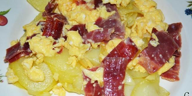 Huevos revueltos con jamón serrano sobre papas fritas