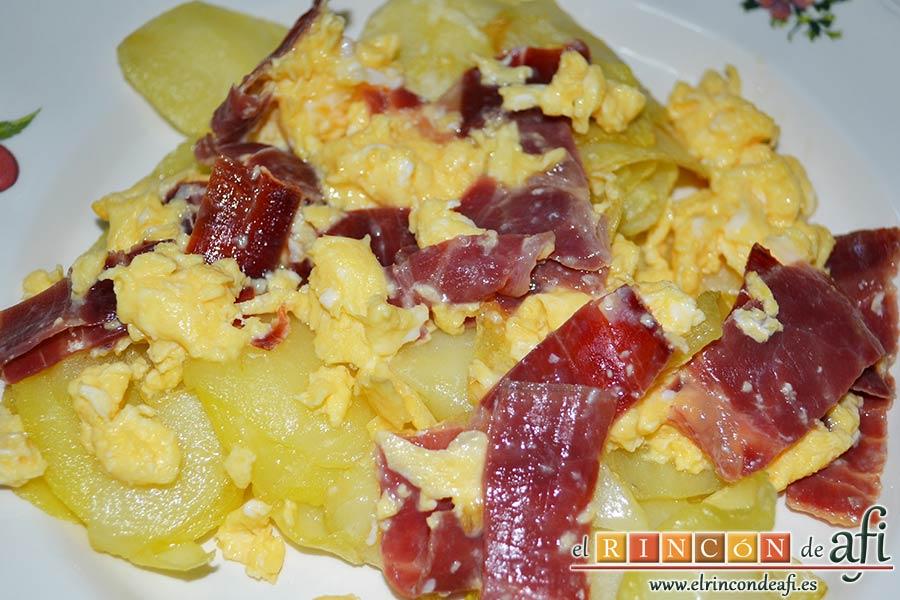 Huevos revueltos con jamón serrano sobre papas fritas, sugerencia de presentación