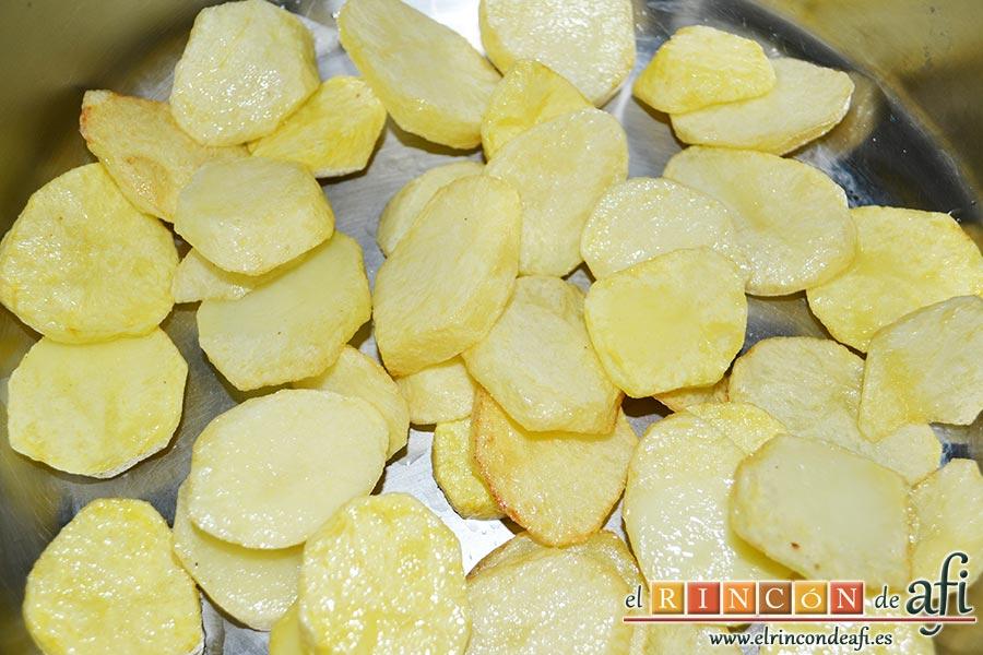 Pollo con verduras y salsa teriyaki, freír las papas cortadas en rodajas y colocar en el fondo de una cacerola
