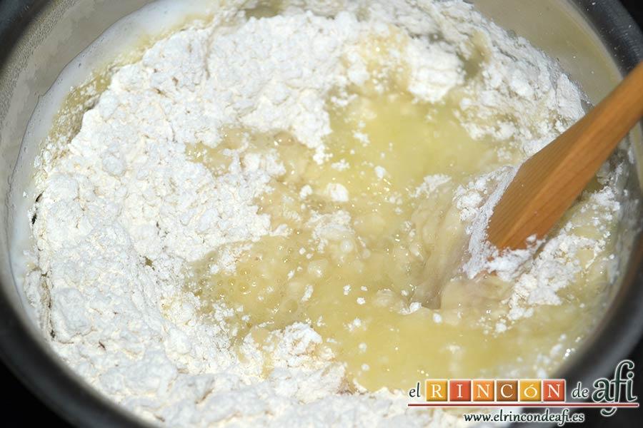 Profiteroles rellenos de nata y cubiertos con chocolate, separar del fuego y añadir toda la harina de golpe