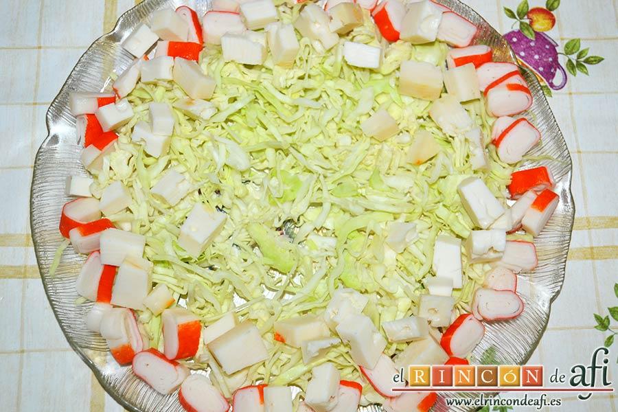 Ensalada con tomate, huevos, queso, col y palitos de cangrejo, hacemos una cama con la col troceada, y disponemos los cubos de queso y los palitos de cangrejo troceados