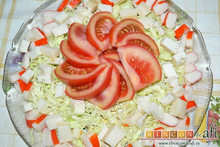 Ensalada con tomate, huevos, queso, col y palitos de cangrejo, colocar los tomates en gajos en el centro