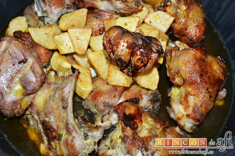 Cabrito estilo Afi, añadir a la carne las papas, la cabeza de ajo y la mitad del aceite de la fritura del cabrito