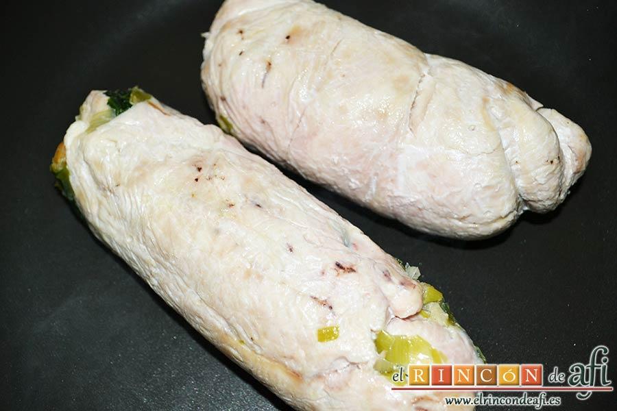 Pechugas de pollo rellenas con espinacas y salsa de queso, poner los rollos en una sartén