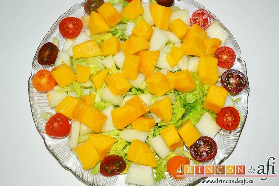 Ensalada de mangas, melón y palitos de cangrejo, pelar y cortar la manga en cubitos y ponerlos sobre la lechuga