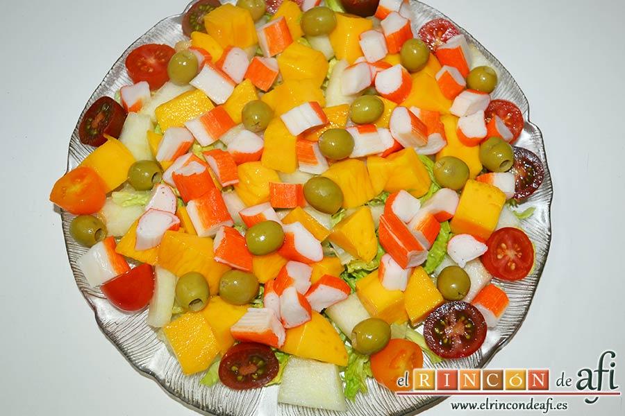 Ensalada de mangas, melón y palitos de cangrejo, añadir las aceitunas y los palitos de cangrejo troceados