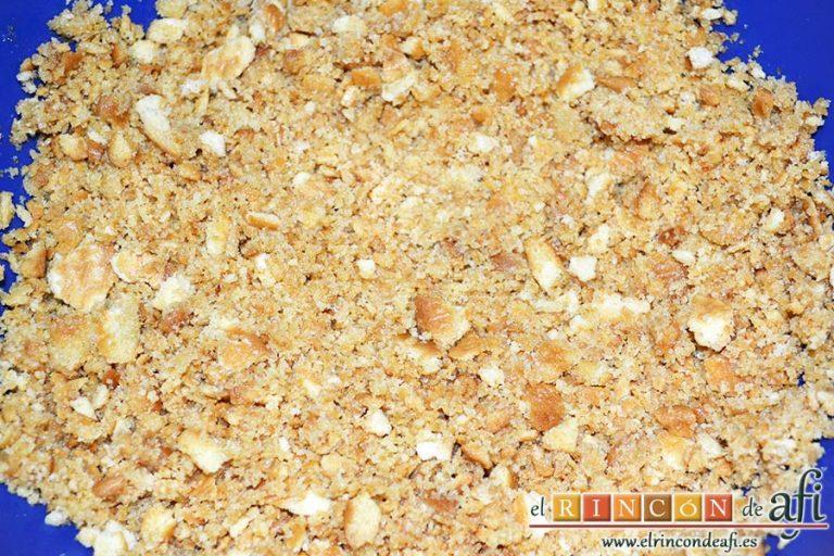 Tarta de quesos con mermelada de frutos rojos, triturar las galletas y los bizcochos mezclándolos con la mantequilla derretida