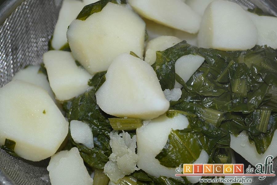 Acelgas con papas y refrito de ajos con jamón serrano, escurrirlas con ayuda de un colador