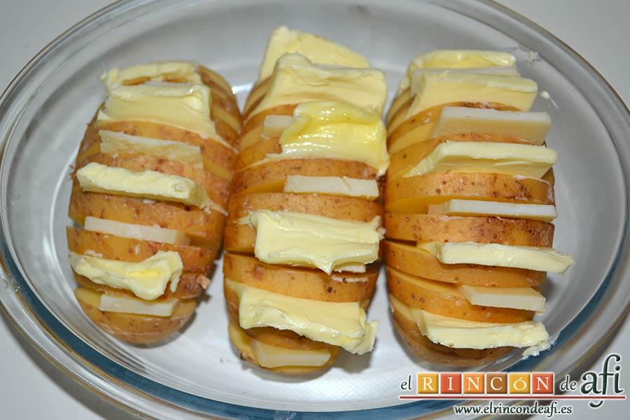 Papas al horno Hasselback, ponemos las papas en una fuente de horno e introducimos en los cortes queso y mantequilla de forma alterna