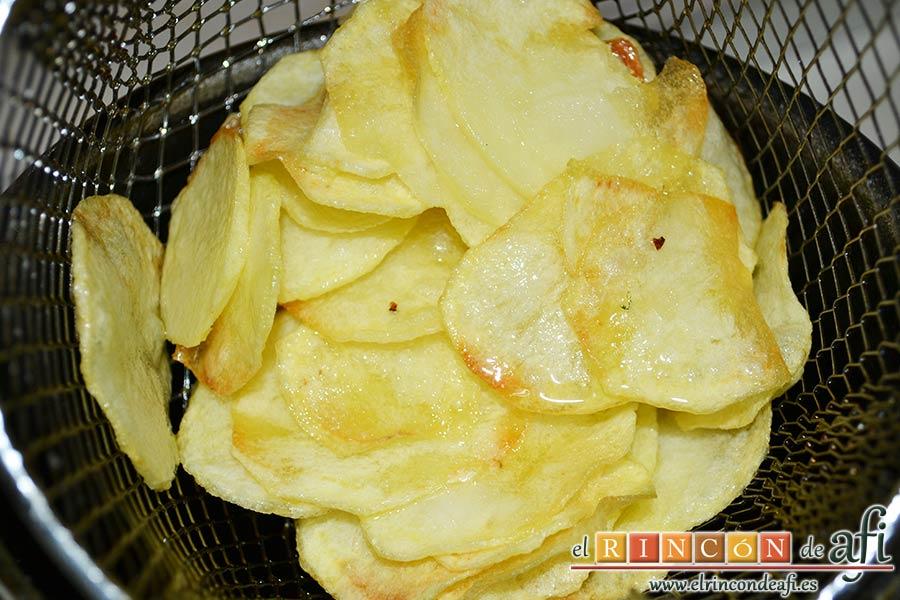 Papas fritas, huevos fritos, bacon y cebollas, freír las papas en una freidora