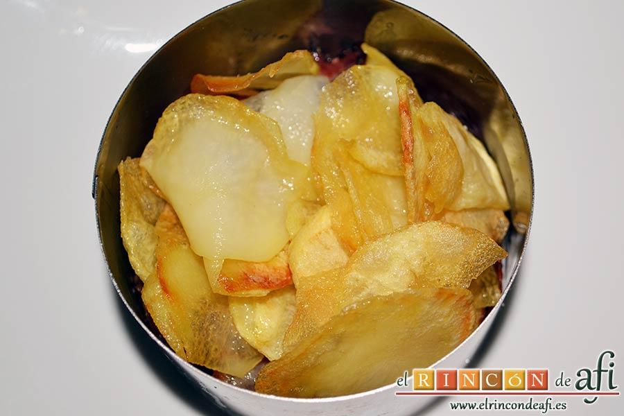 Papas fritas, huevos fritos, bacon y cebollas, ponemos una buena cama de papas