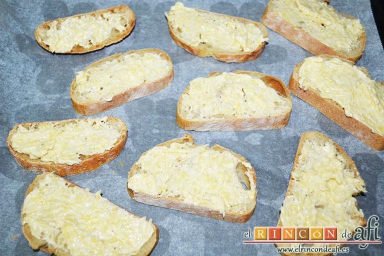 Pan de ajo gratinado, cortar en rodajas el pan y untarlo generosamente con la mantequilla