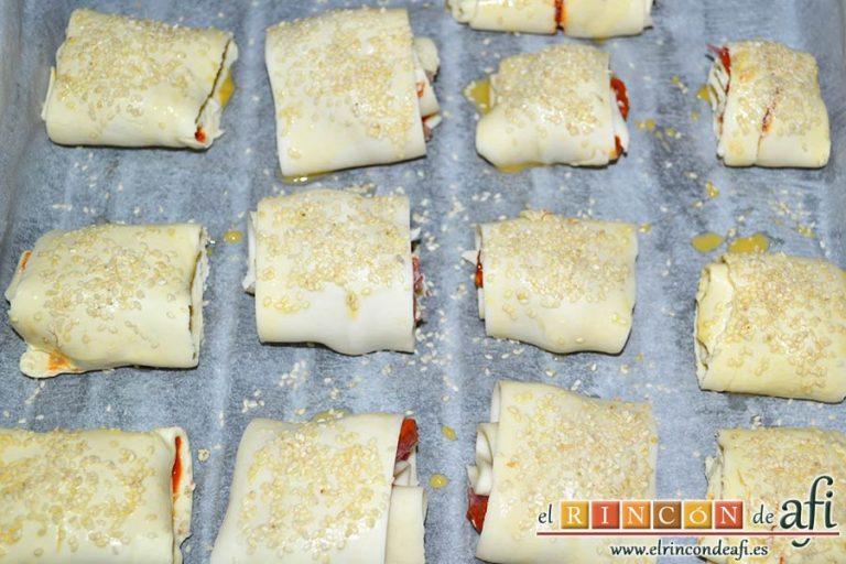 Rollitos de hojaldre rellenos de crema de pimientos y salchichas frescas, pintar los rollitos con huevo batido y espolvorear con semillas de sésamo, y hornear