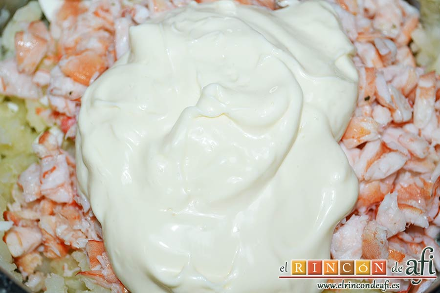 Ensaladilla con langostinos, cangrejo ruso, papas y huevos, añadir la mayonesa