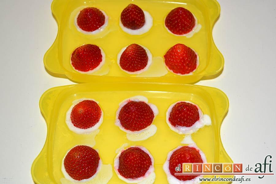Bombones helados de fresa y yogur, sacar la cubitera del congelador y poner encima de cada espacio una fresa