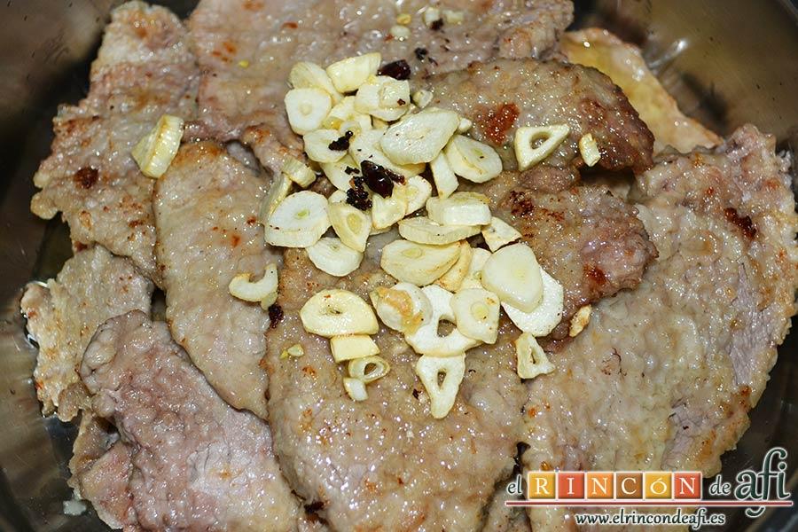 Filetes de ternera al cava, echar sobre la carne los ajos y las guindillas