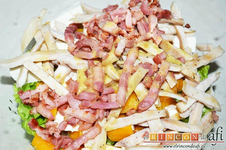 Ensalada con vegetales, pollo, bacon y queso, aliñar la ensalada y mezclar bien