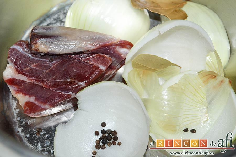 Garbanzos con berenjenas, ponemos en una olla exprés los cascos de cebolla, la punta de jamón, los granos de pimienta negra y las hojitas de laurel