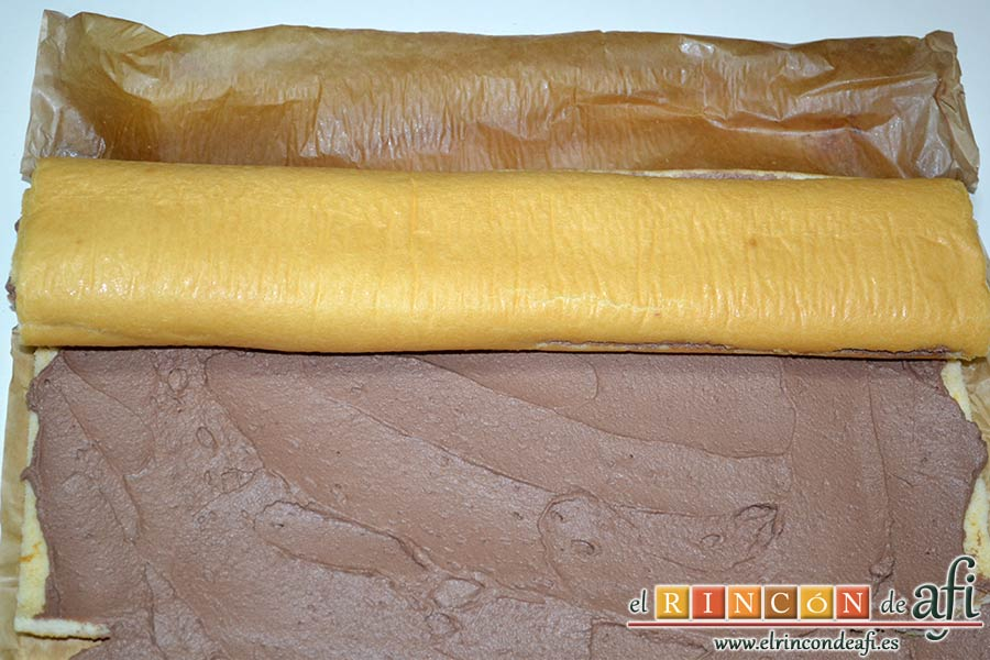 Brazo gitano relleno de trufa, ir enrollando el bizcocho con ayuda de un papel de horno